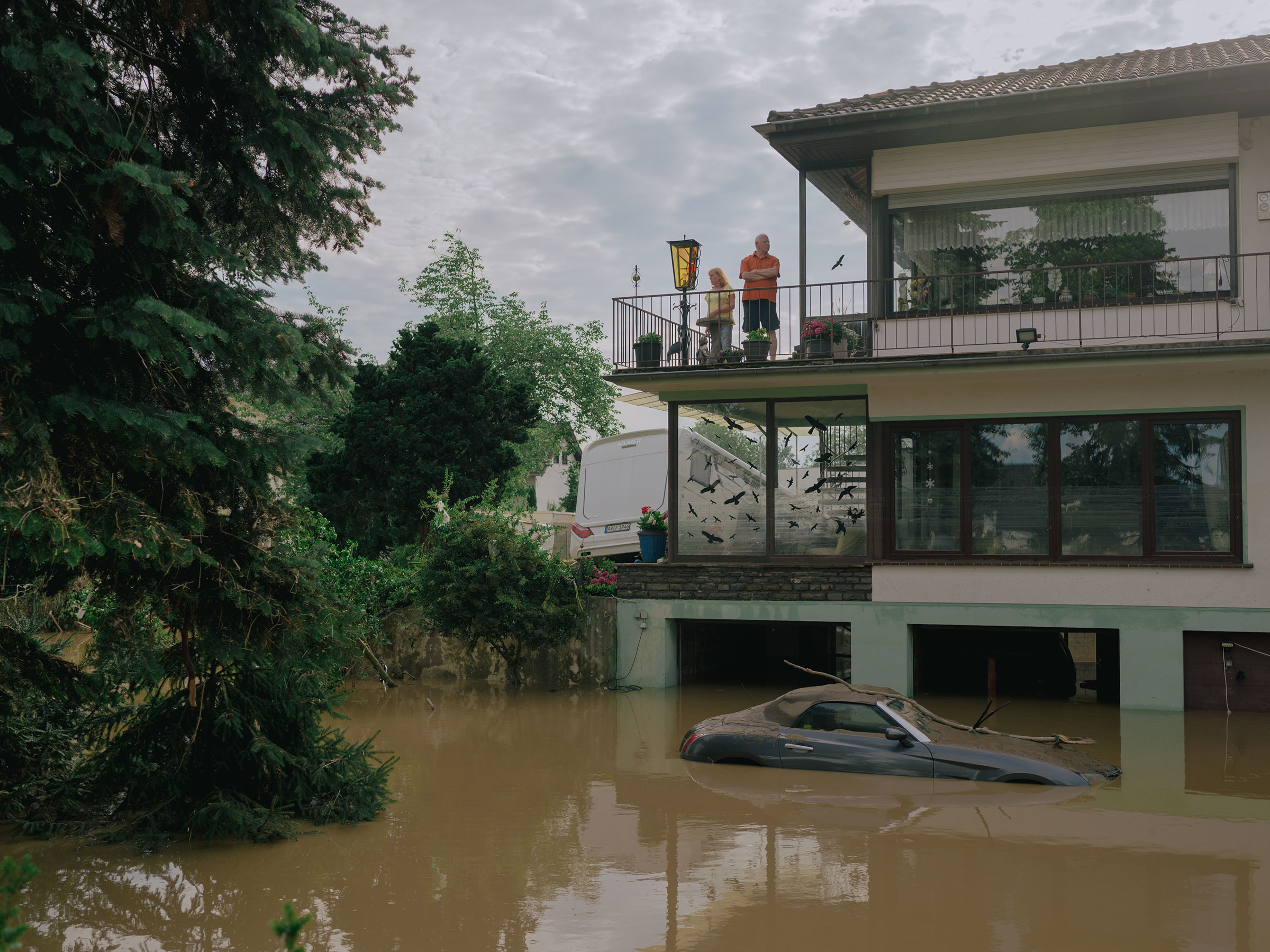 People stand on a balcony above the floodwaters in Ahrweiler, Germany, July 15, 2021.
