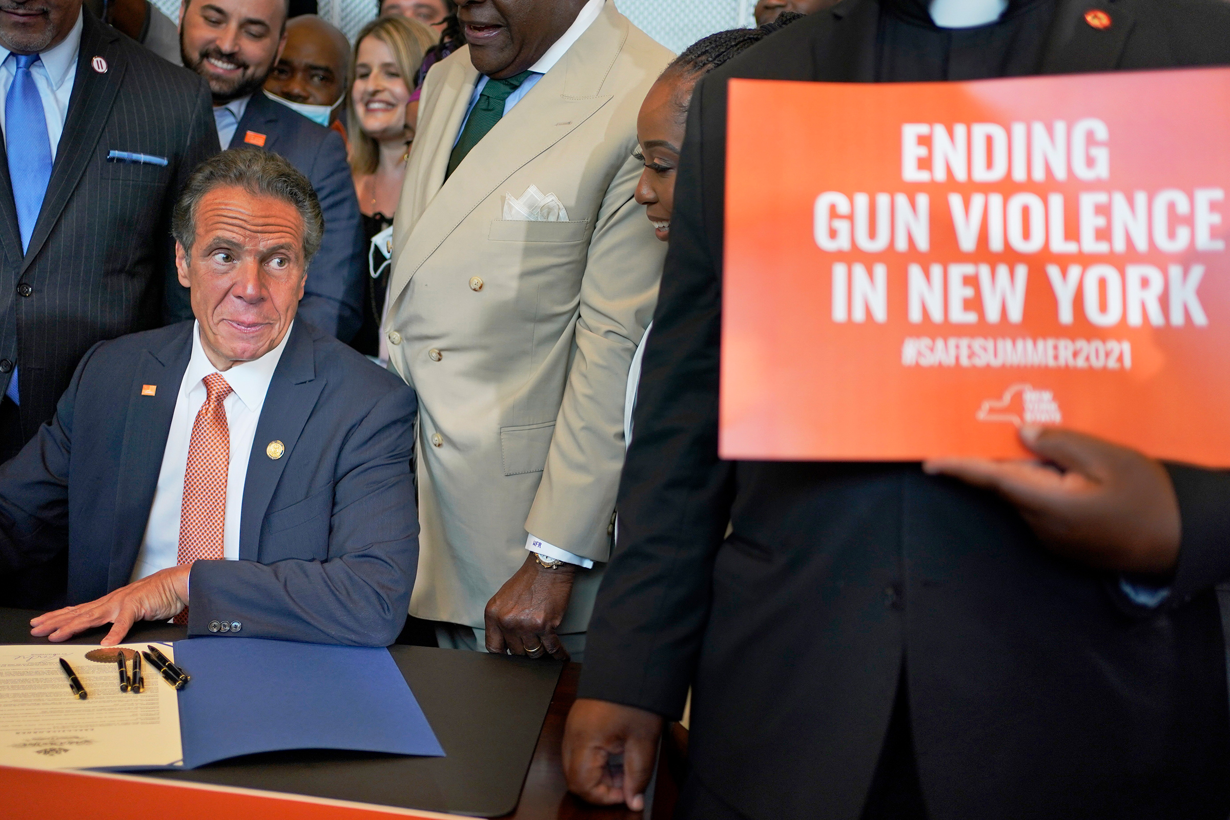 Surrounded by supporters and advocates, New York Governor Andrew Cuomo signs legislation on gun control in New York on July 6. Cuomo signed two pieces of legislation to combat gun violence in New York state.
