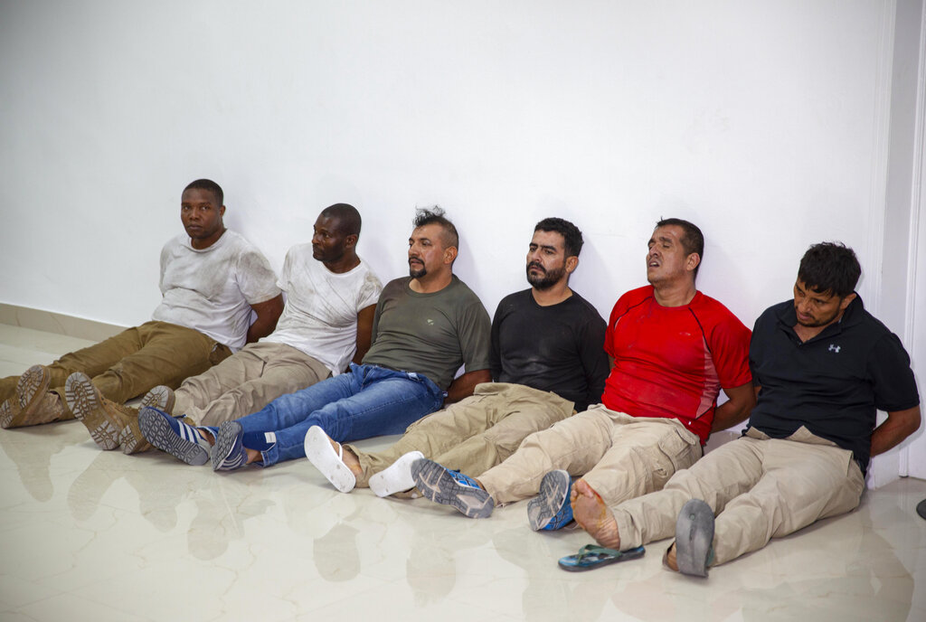Suspects in the assassination of Haiti's President Jovenel Moise, among them Haitian-American citizens James Solages, left, and Joseph Vincent, second left, are shown to the media at the General Direction of the police in Port-au-Prince, Haiti, Thursday, July 8, 2021. Moise was assassinated in an attack on his private residence early Wednesday.