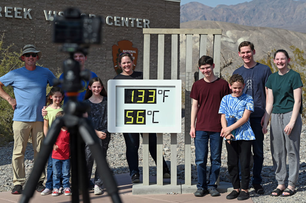 People visit the unofficial thermometer reading 133 degrees Fahrenheit/56 degrees Celsius at Furnace Creek Visitor Center on July 11, 2021 in Death Valley National Park, California.