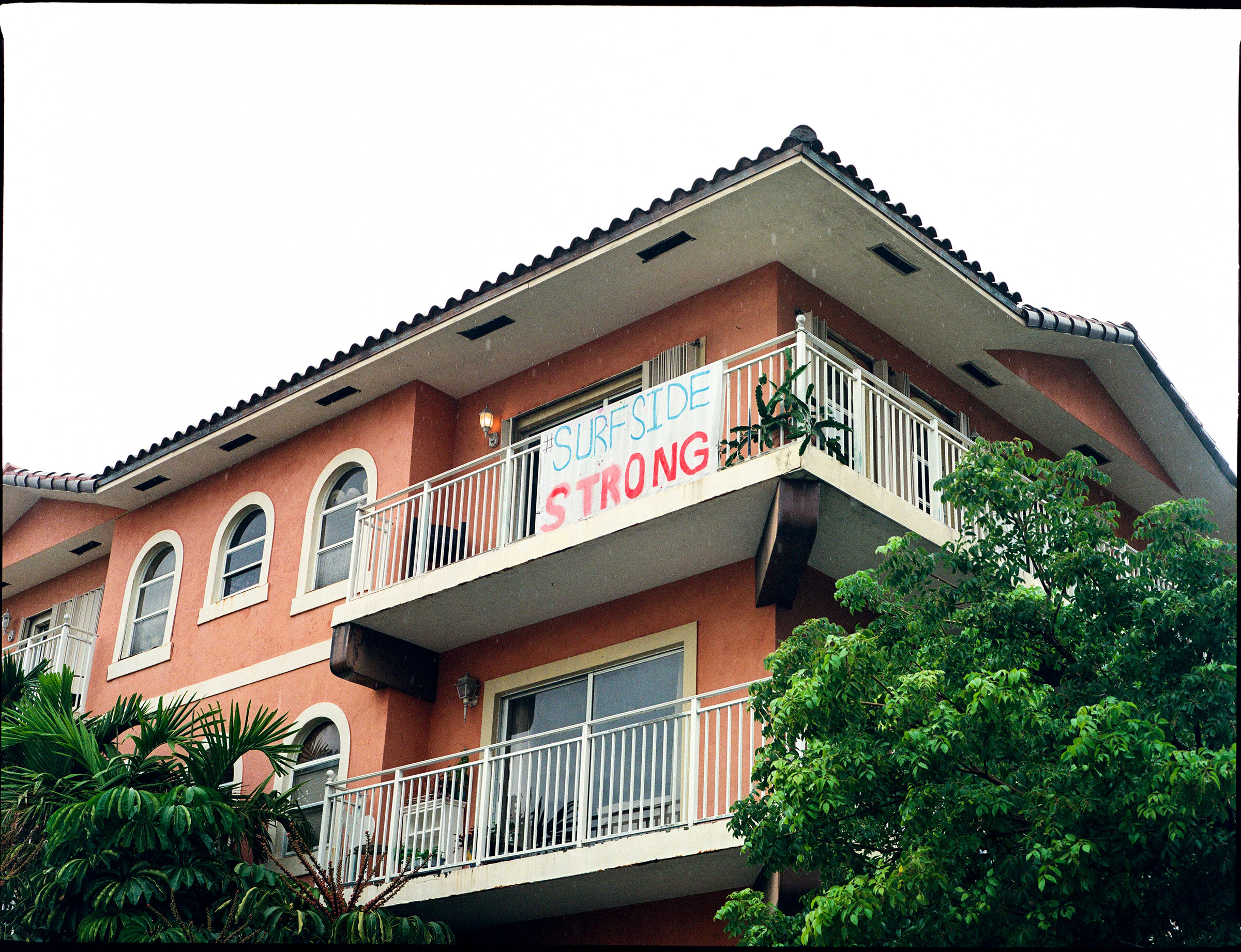 A sign, that reads  Surfside Strong , hangs off of the balcony of a nearby apartment building.