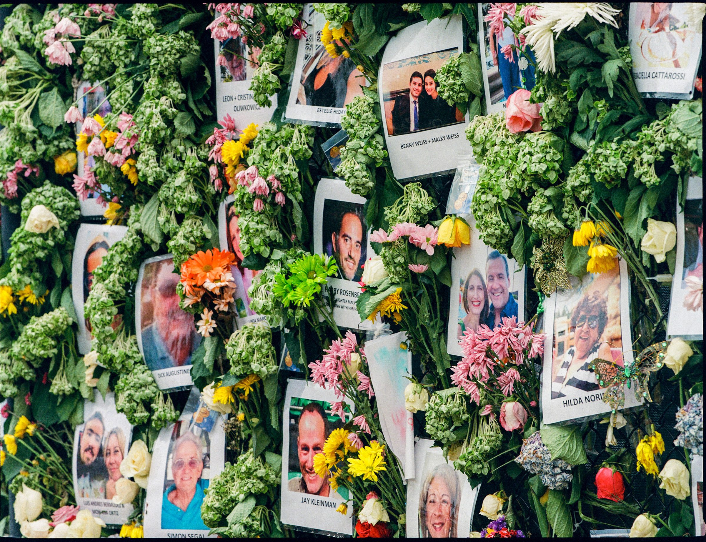 A memorial wall, set up on a nearby tennis court fence, full of posters of missing victims on June 30.