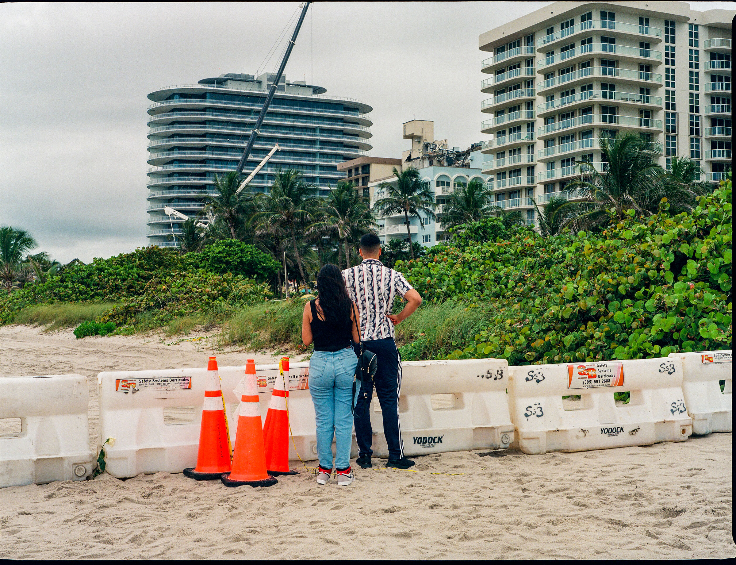 People look at the collapsed Champlain Towers South building from the beach in Surfside, Fla. on June 30, 2021.