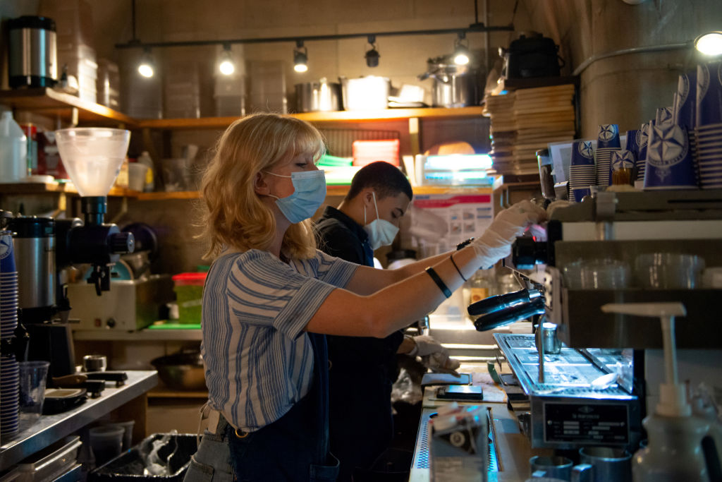 A barista wearing a mask prepares coffee on August 23, 2020, during New York's Phase 4 of re-opening following restrictions imposed to slow the spread of coronavirus