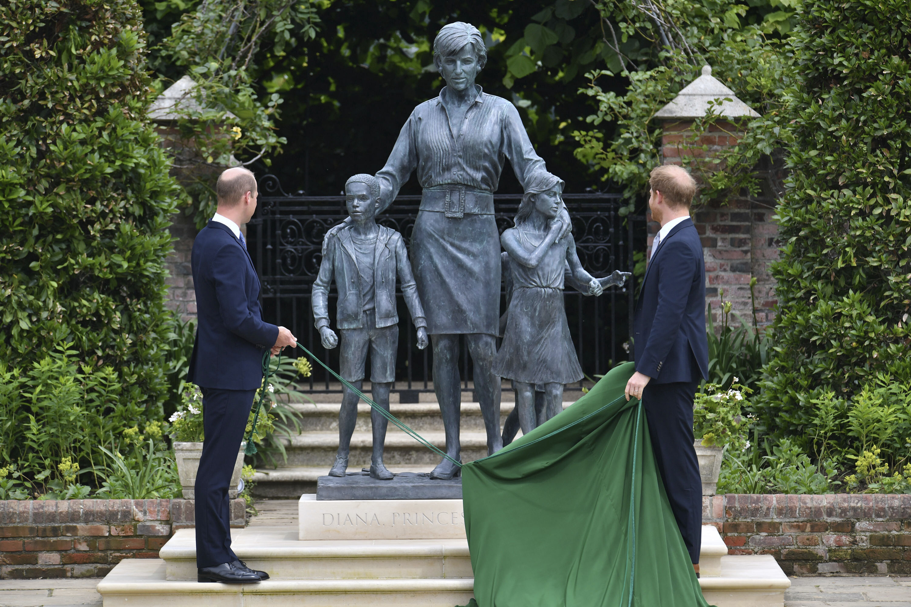 Britain's Prince William, left and Prince Harry unveil a statue they commissioned of their mother Princess Diana,  on what woud have been her 60th birthday, in the Sunken Garden at Kensington Palace, London, Thursday July 1, 2021.