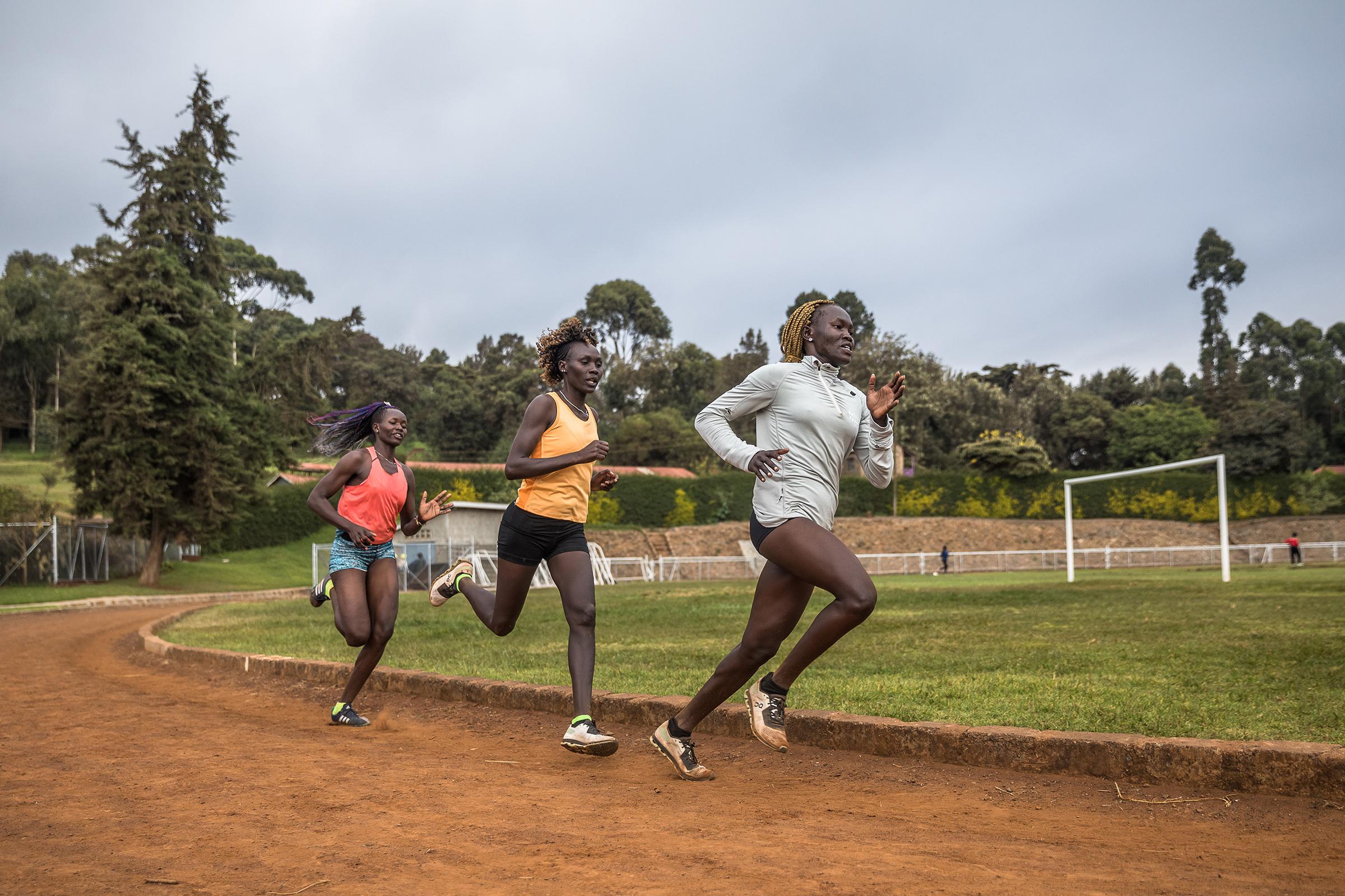 Refugee athletes Atalena Nopule (left), Angelina Nadai Lohalith and                    Rose Nathike Lokonyen run laps at the training camp in Ngong, Kenya.