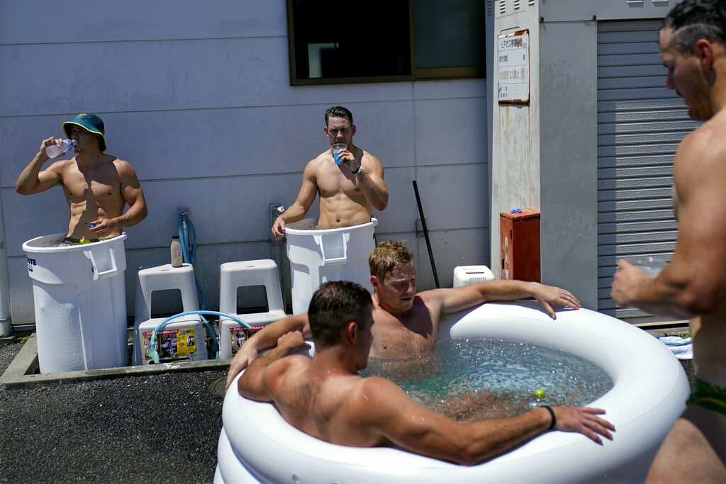 Members of Australia's men's rugby sevens team soak in ice baths following practice in the midday heat at the Tokyo 2020 Olympics, in Tokyo, on July 23, 2021.