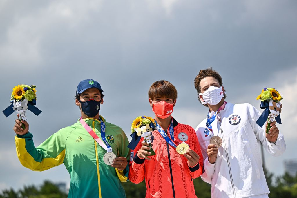 Gold medallist Japan's Yuto Horigome (C), silver medallist Brazil's Kelvin Hoefler (L) and bronze medallist Jagger Eaton of the US pose on the podium at the end of the men's street prelims during the Tokyo 2020 Olympic Games at Ariake Sports Park Skateboarding in Tokyo on July 25, 2021.