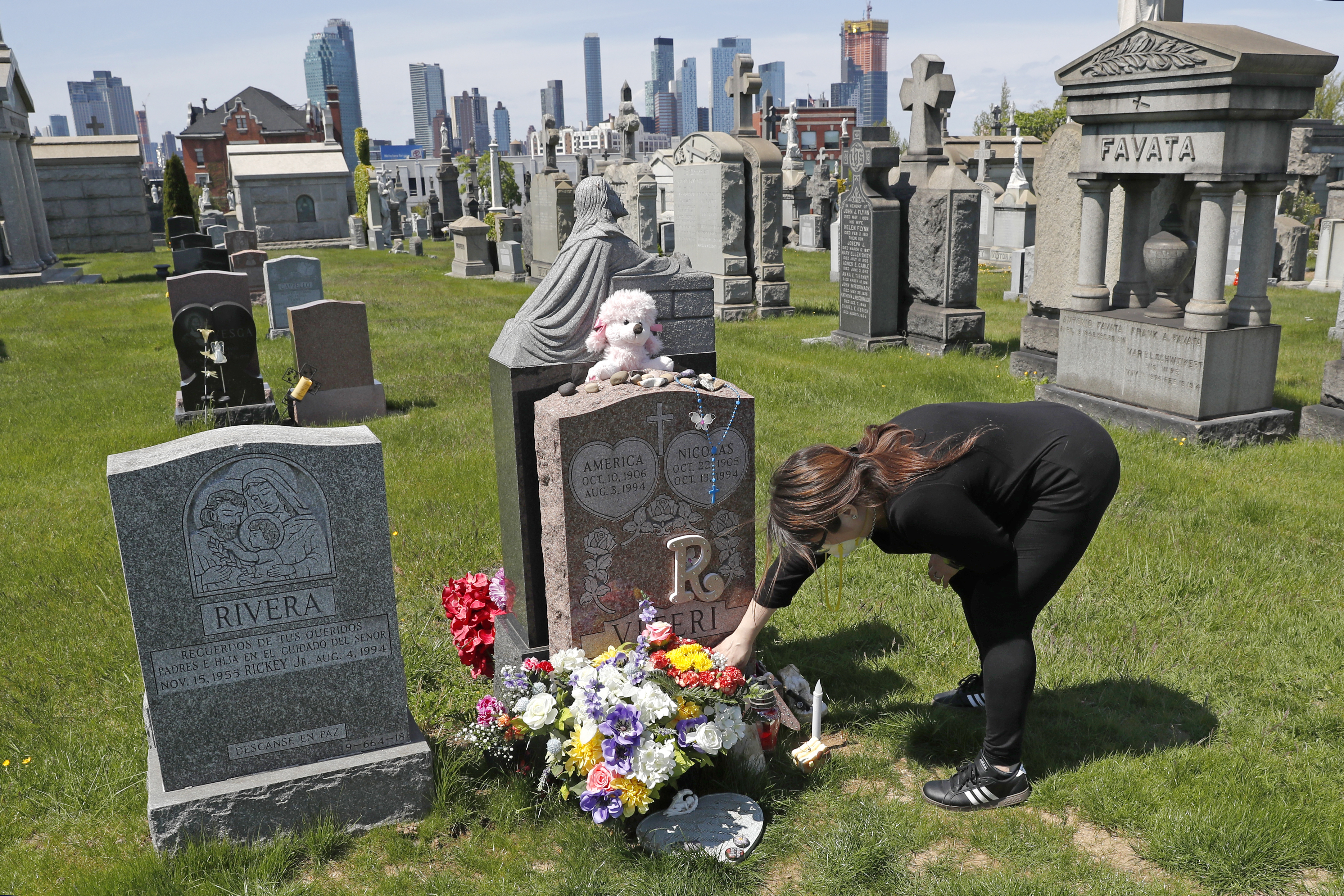 In this Sunday, May 10, 2020 file photo, Sharon Rivera adjusts flowers and other items left at the grave of her daughter, Victoria, at Calvary Cemetery in New York, on Mother's Day.