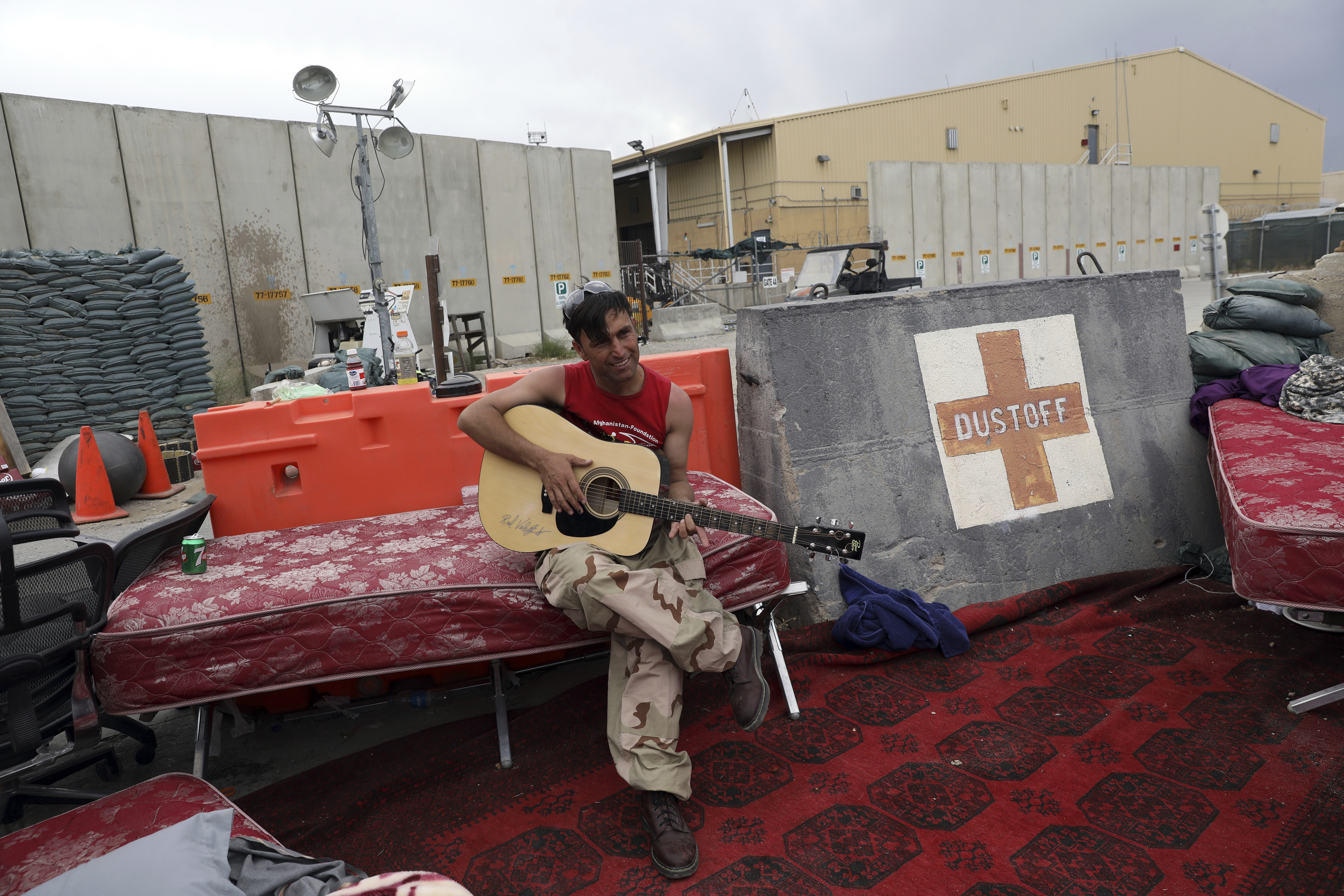 An Afghan soldier plays a guitar that was left behind after the American military departed Bagram air base, in Parwan province north of Kabul, Afghanistan, Monday, July 5, 2021. The U.S. left Afghanistan's Bagram Airfield after nearly 20 years, winding up its  forever war,  in the night, without notifying the new Afghan commander until more than two hours after they slipped away.