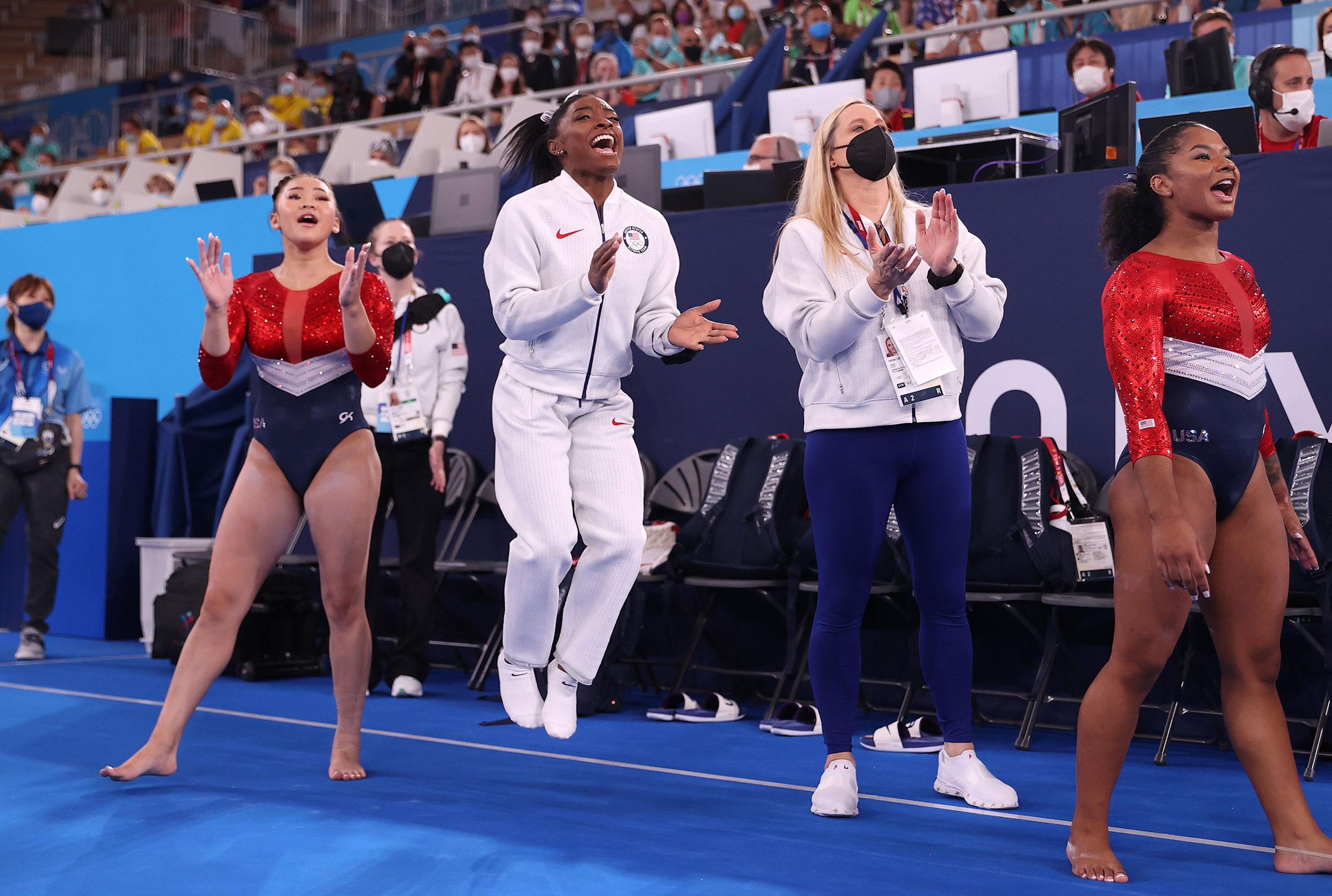 Sunisa Lee, Simone Biles, coach Cecile Landi and Jordan Chiles of Team United States cheer as Grace McCallum competes in floor routine during the Women's Team Final on July 27.