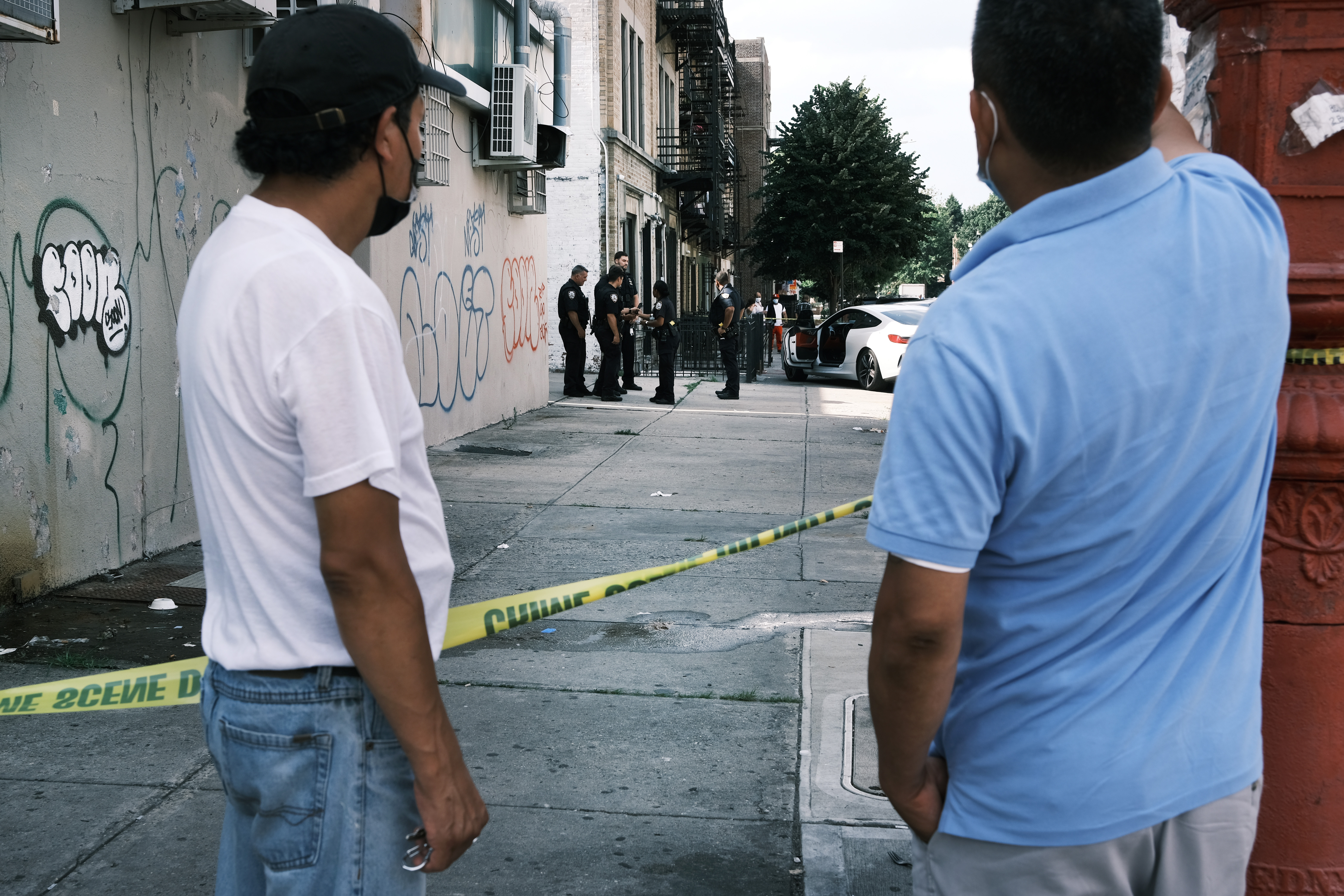 People look on as police converge on the scene of a shooting in Brooklyn, one of numerous during the day, on July 14, 2021 in New York City.