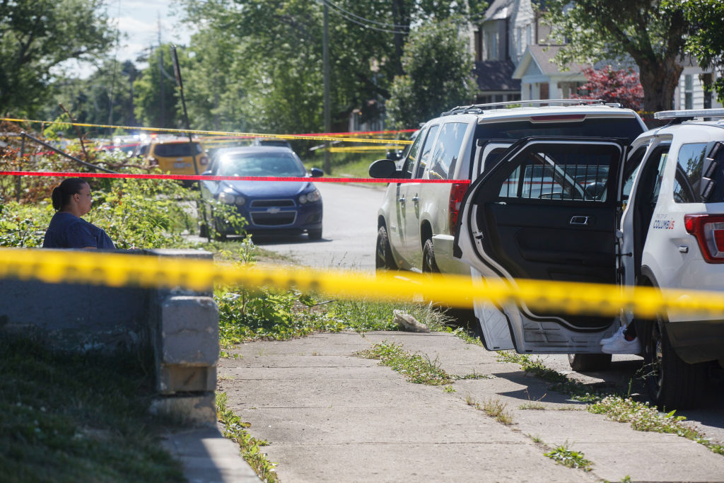 A woman sits at the scene of a police- involved shooting in Columbus, Ohio on June 22.