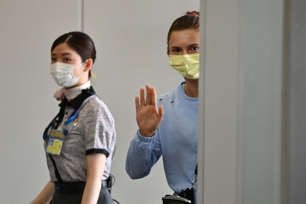 Belarus athlete Krystsina Tsimanouskaya waves goodbye as she boards a flight at Narita International Airport outside Tokyo on Aug. 4, 2021, after traveling from the Polish embassy, where she had spent the past two nights following claims her team tried to force her to return home after she criticized her coaches during the Tokyo Olympic Games.