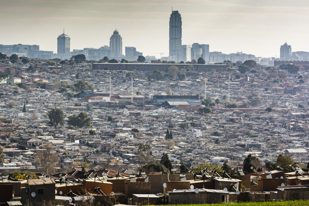 Residential housing stands in the Alexandra township as the skyscraper office buildings in the Sandton area stand on the skyline beyond in Johannesburg, South Africa, on Thursday, June 11, 2020.