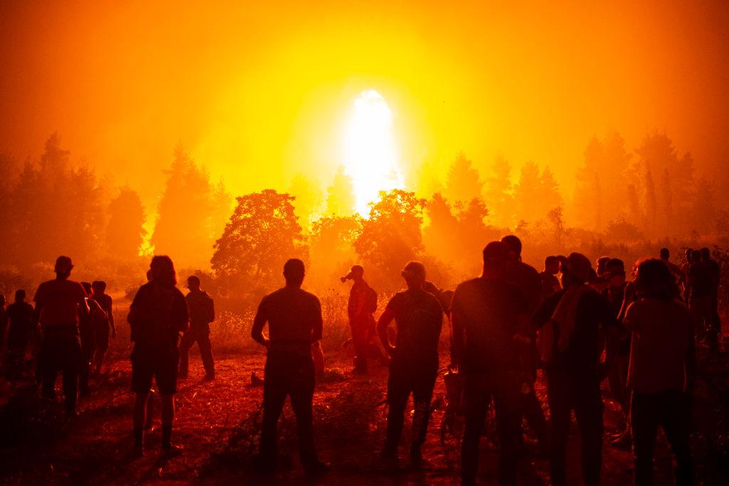 يتجمع الشباب والمتطوعون المحليون في حقل مفتوح وينتظرون لدعم رجال الإطفاء أثناء حريق غابات بالقرب من قرية كاماترياديس ، بالقرب من إستيايا ، شمال جزيرة إيفيا (إيبويا) في 9 أغسطس 2021.