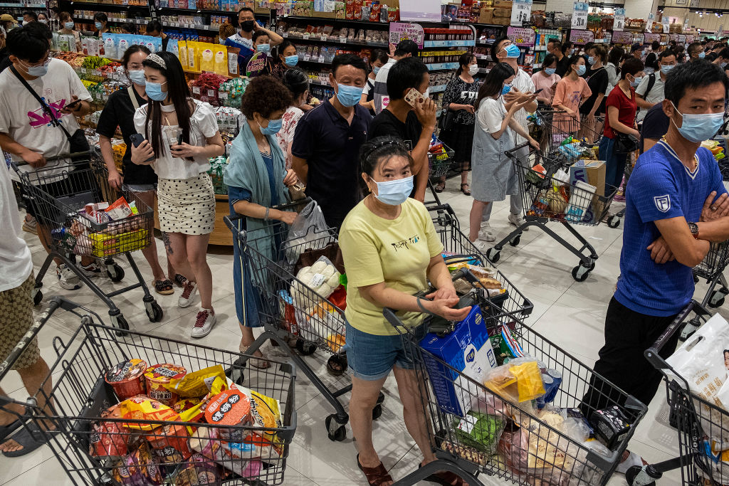 People wear protective masks as they line up to pay in a supermarket on August 2, 2021 in Wuhan, Hubei Province, China. According to media reports, seven migrant workers returned positive COVID-19 nucleic acid tests. Wuhan has not reported locally transmitted cases for over a year.