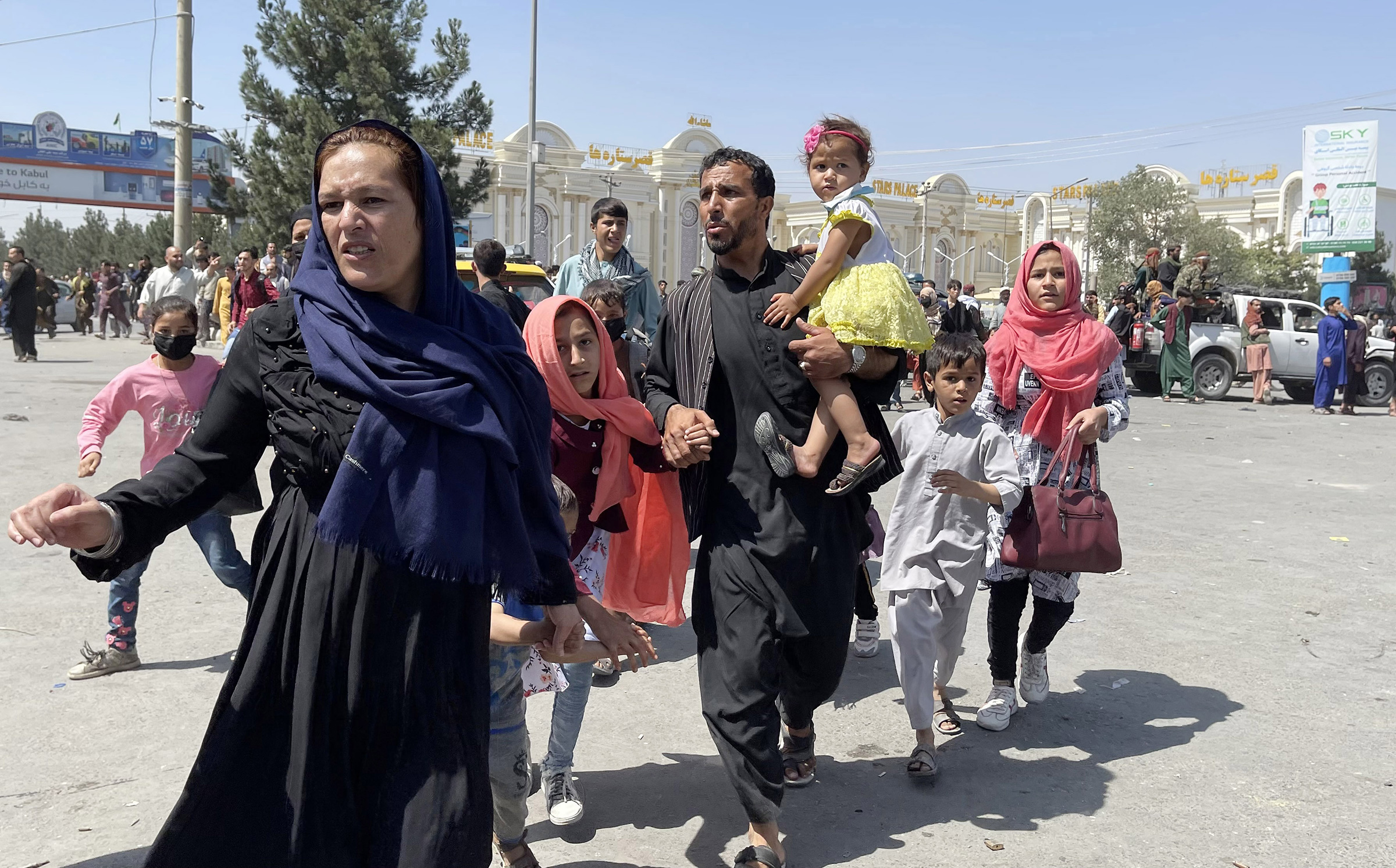 An Afghan family rushes to the Hamid Karzai International Airport as they flee Kabul, Afghanistan, on August 16, 2021.