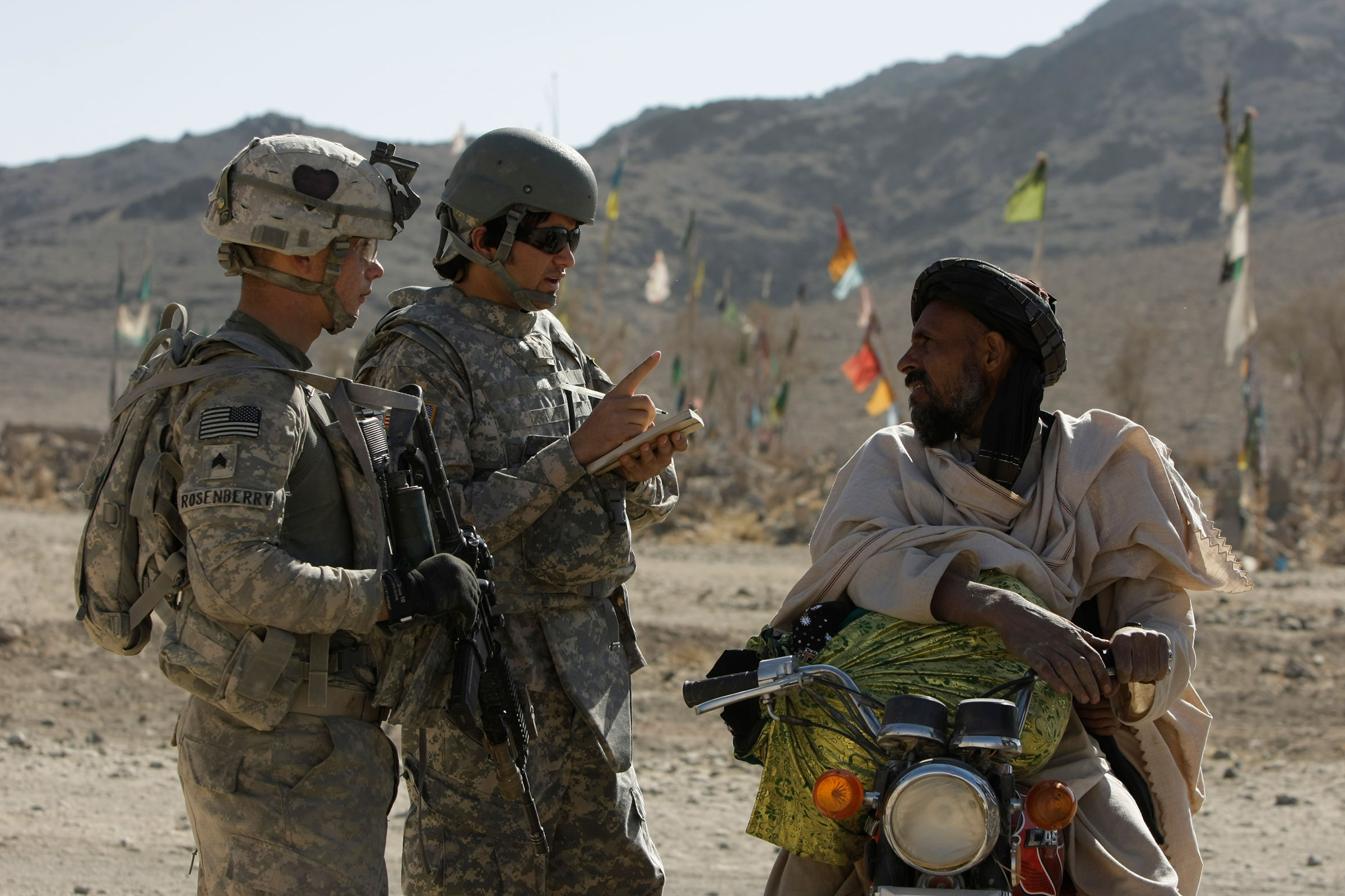 US Army Sgt. Skyler Rosenberry of Pennsylvania, left, and an Afghan interpreter, center, from First Battalion, 502nd Infantry Regiment, 101st Airborne Division speak to an Afghan man during a foot patrol in West Now Ruzi village, district Panjwai, Afghanistan's Kandahar province, Wednesday, Nov. 24, 2010.