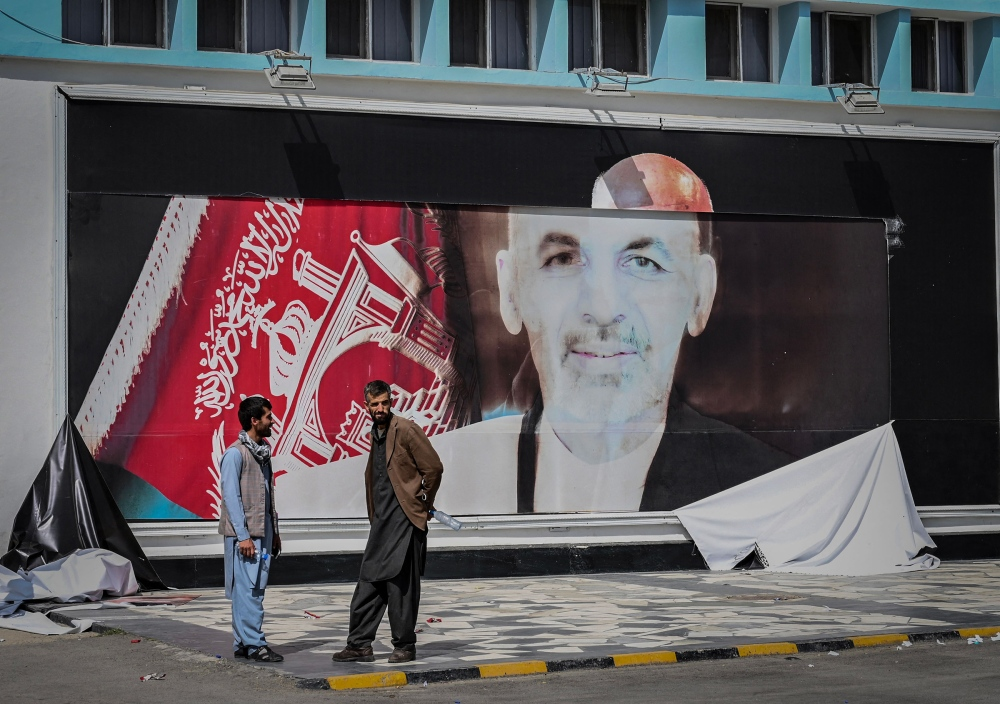 Men stand next to a torn poster of Afghan President Ashraf Ghani at the Kabul airport on Aug. 16, 2021, the day after Ghani fled the country and the Taliban gained control of the presidential palace.