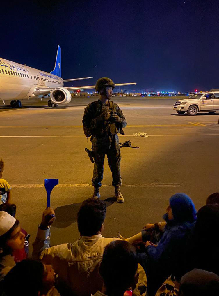 جندي من الجيش الأمريكي يحرس بينما ينتظر الأفغان المغادرة من مطار كابول في 16 أغسطس 2021.