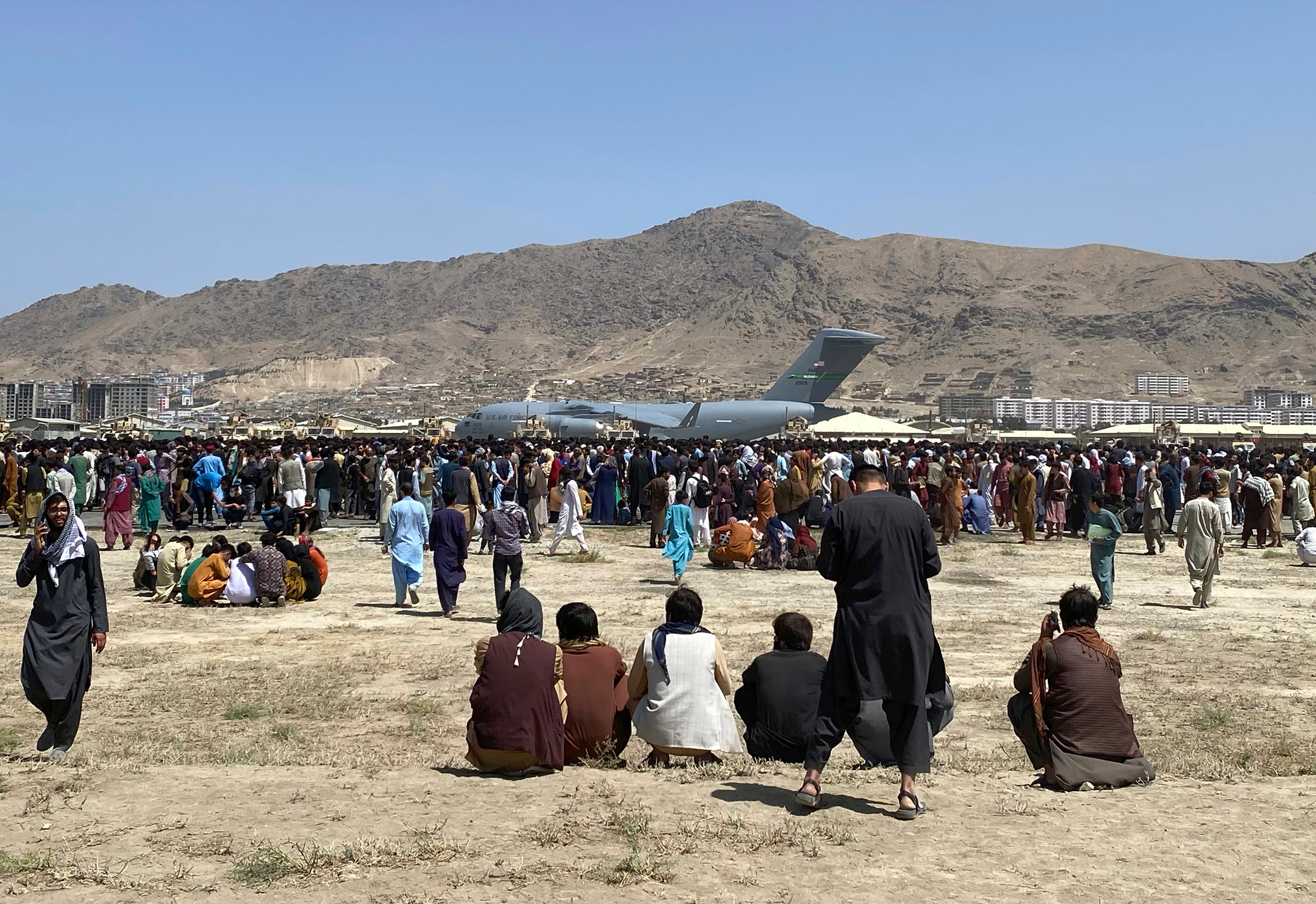 Hundreds of people gather near a U.S. Air Force C-17 transport plane at a perimeter at the international airport in Kabul on Monday, Aug. 16.