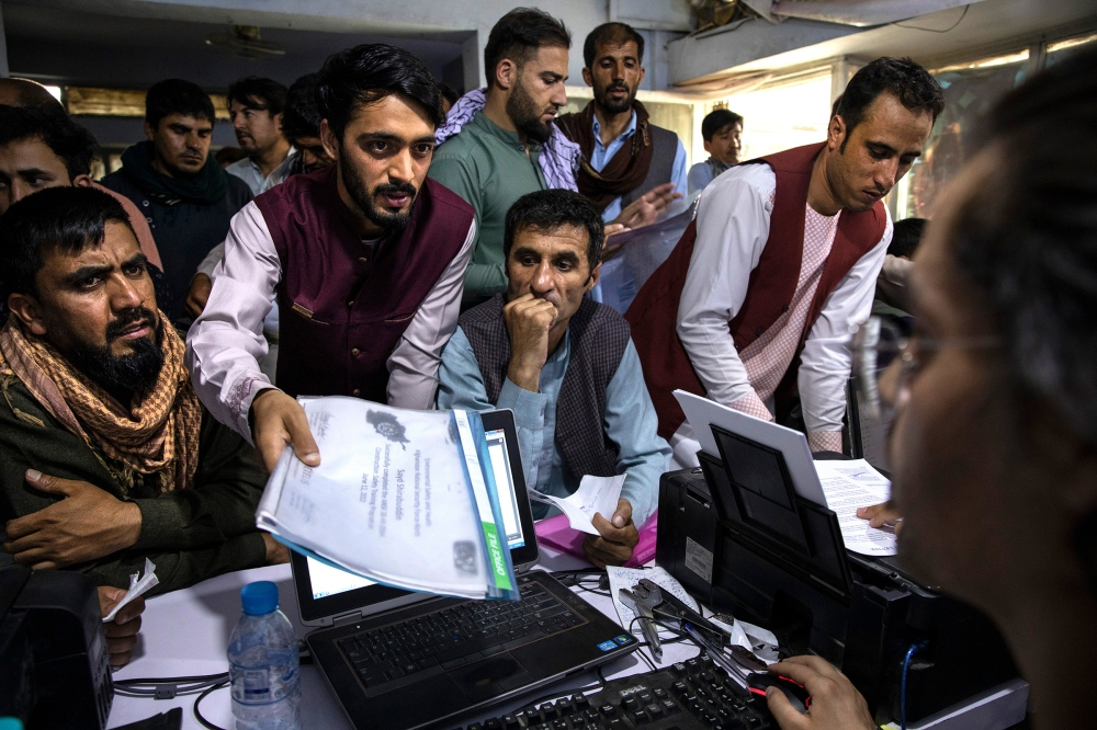 Men crowd into an Internet café while seeking help with applications for the Special Immigrant Visa program in Kabul on Aug. 8, 2021.