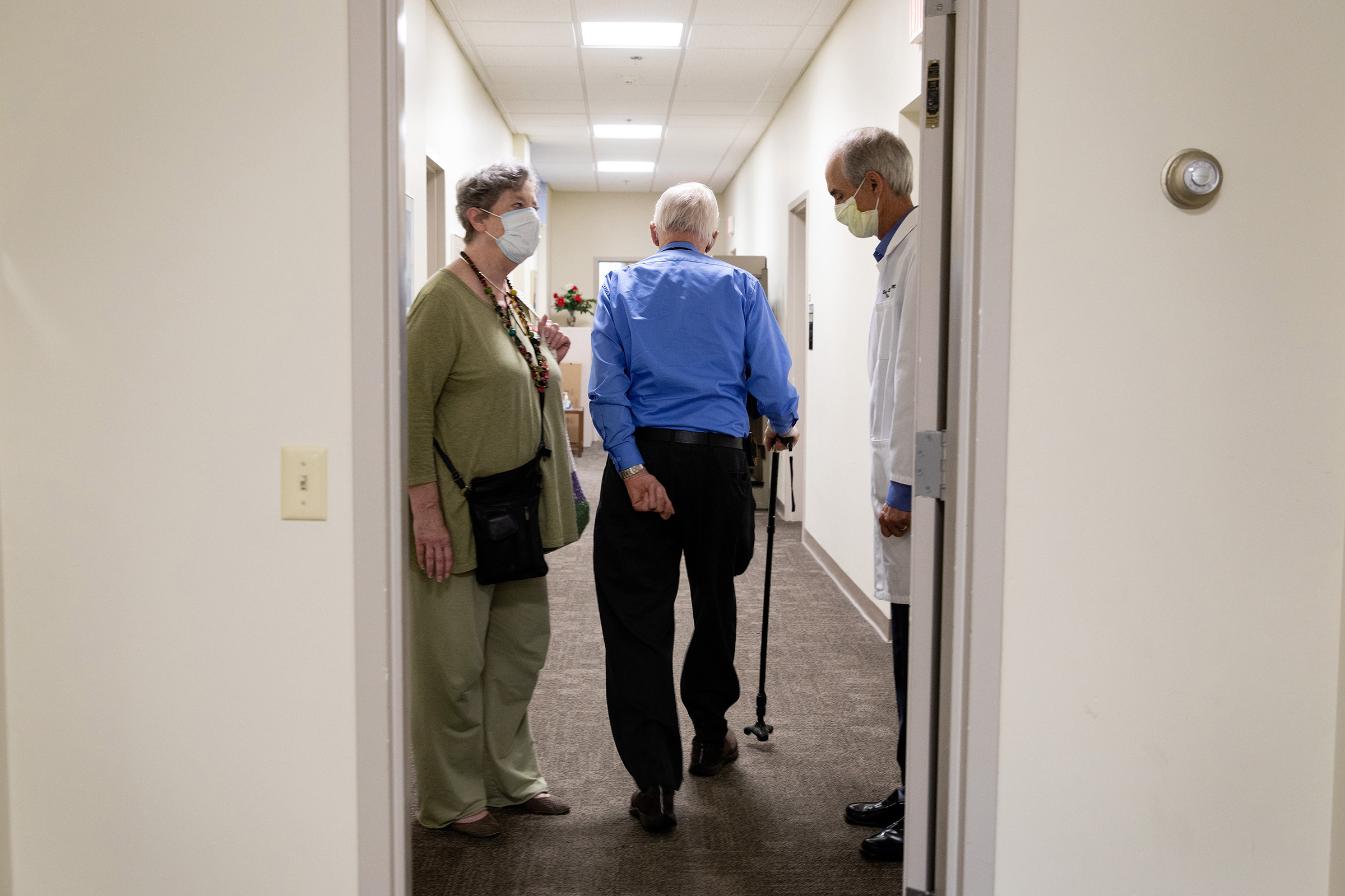 Henry Magendantz, center, a participant in the clinical trial of the experimental Alzheimer's drug, aducanumab, with his wife, Kathy Jellison, and Dr. Stephen Salloway, leaving the hospital after receiving an infusion in Providence, R.I., on May 27, 2021.