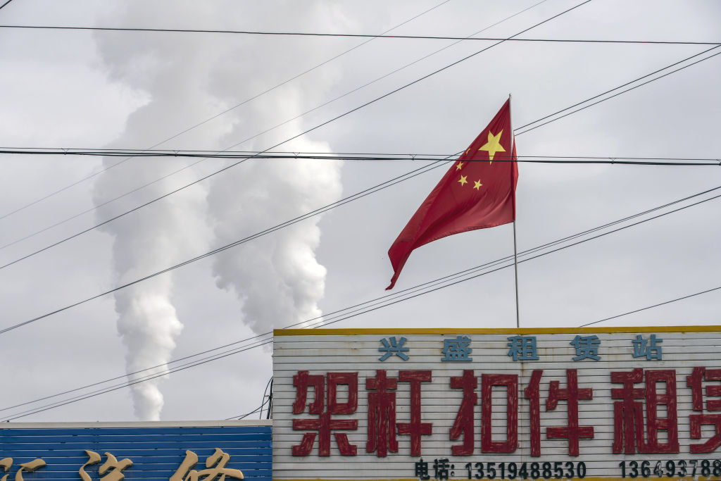 The Chinese flag flies in front of exhaust rising from a coal fired power plant in Jiayuguan, Gansu province, China, on April 1, 2021.