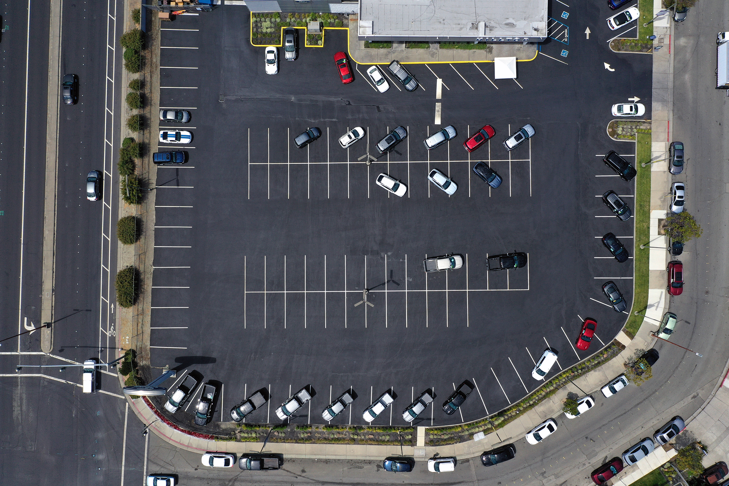 In an aerial view, the sales lot at Hilltop Ford is nearly empty on July 09, 2021 in Richmond, California. The global microchip shortage continues to impact the automobile supply chain and is causing the price of new cars to increase as inventory dwindles.