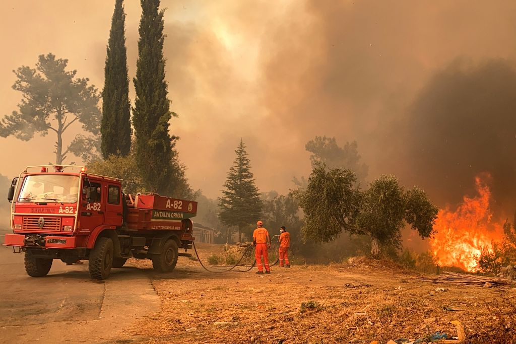 A firefighter battles with fire during a massive wildfire which engulfed a Mediterranean resort region on Turkey's southern coast near the town of Manavgat on July 29, 2021.