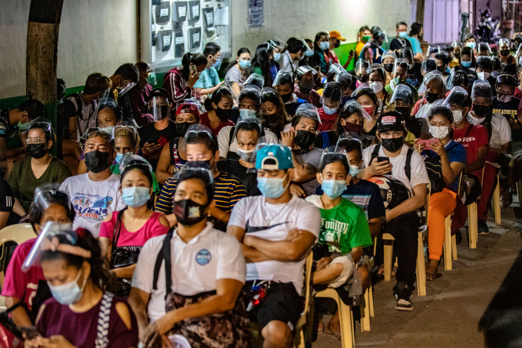 People hoping to get vaccinated against COVID-19 sit while queuing outside a vaccination site on August 08, 2021 in Las Pinas, Metro Manila, Philippines.