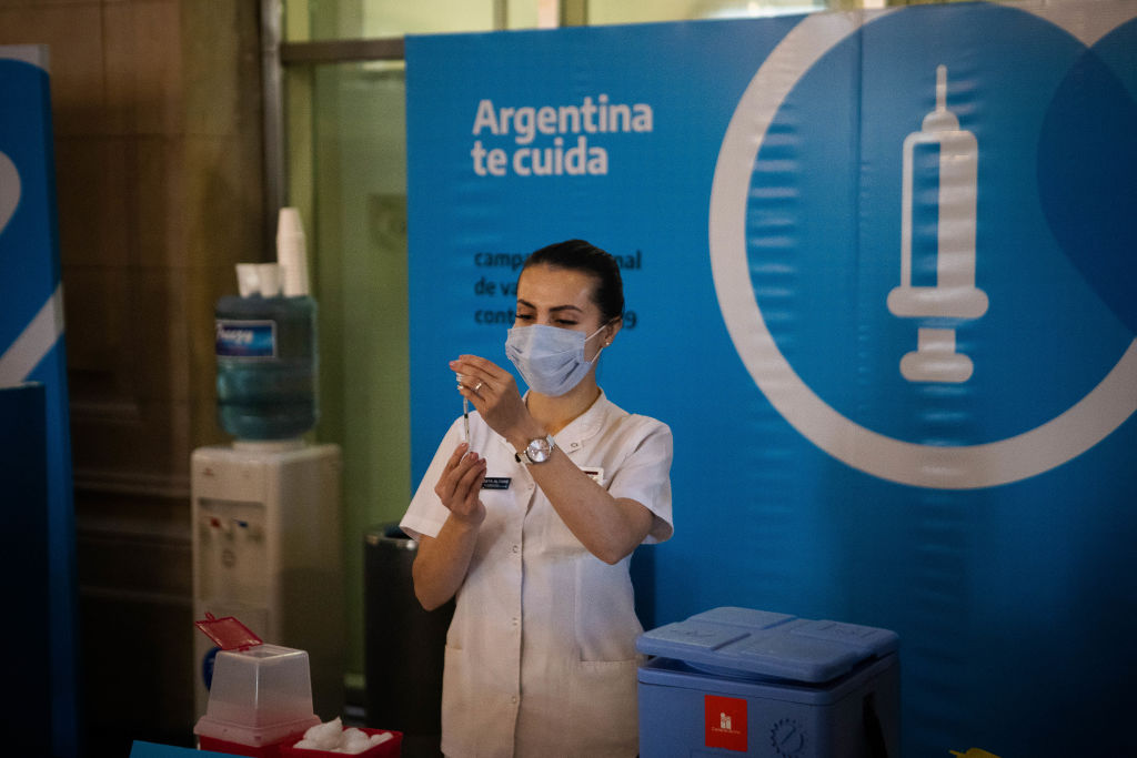 A member of the Armed Forces prepares a dose of the AstraZeneca coronavirus disease (COVID-19) vaccine obtained under the COVAX scheme, at the CCK Cultural Centre (Centro Cultural Kirchner), in Buenos Aires, Argentina June 15, 2021.