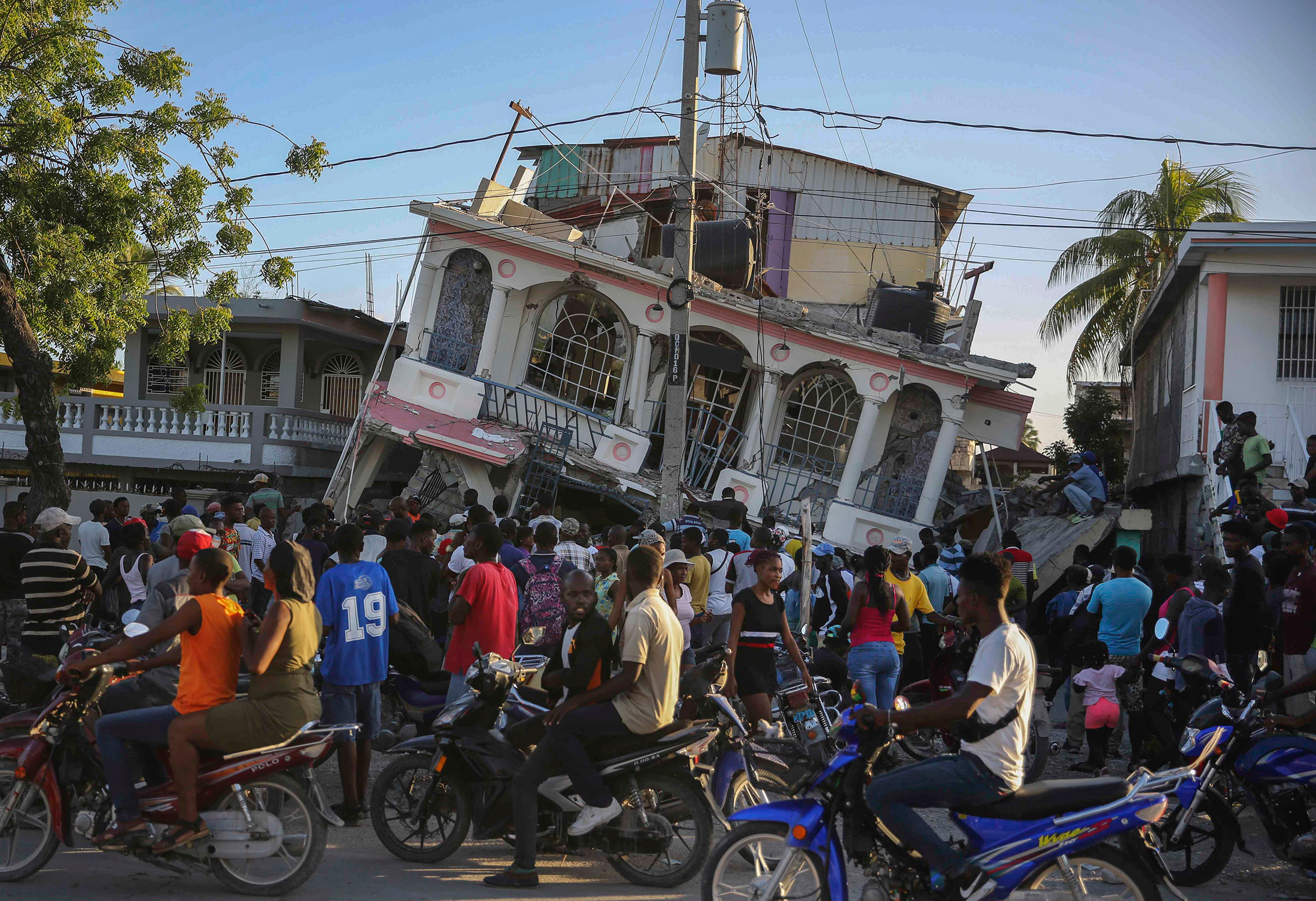 People gather outside the Petit Pas Hotel, destroyed by the earthquake in Les Cayes, on Aug. 14.