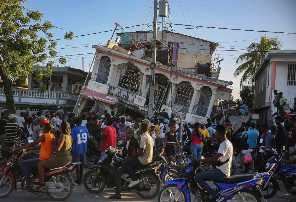 People gather outside the Petit Pas Hotel, destroyed by the earthquake in Les Cayes, Haiti, Aug. 14.