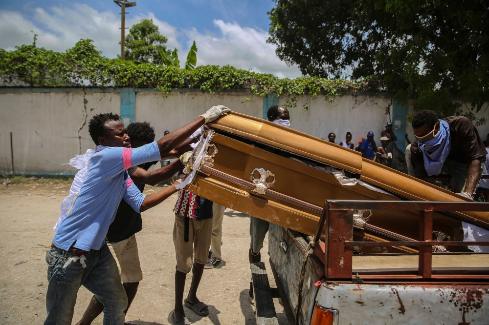 Men load into the bed of a truck the coffin containing the remains of Francois Elmay after recovering his body from the rubble of a home destroyed in the earthquake, in Les Cayes, Haiti, Aug. 18.