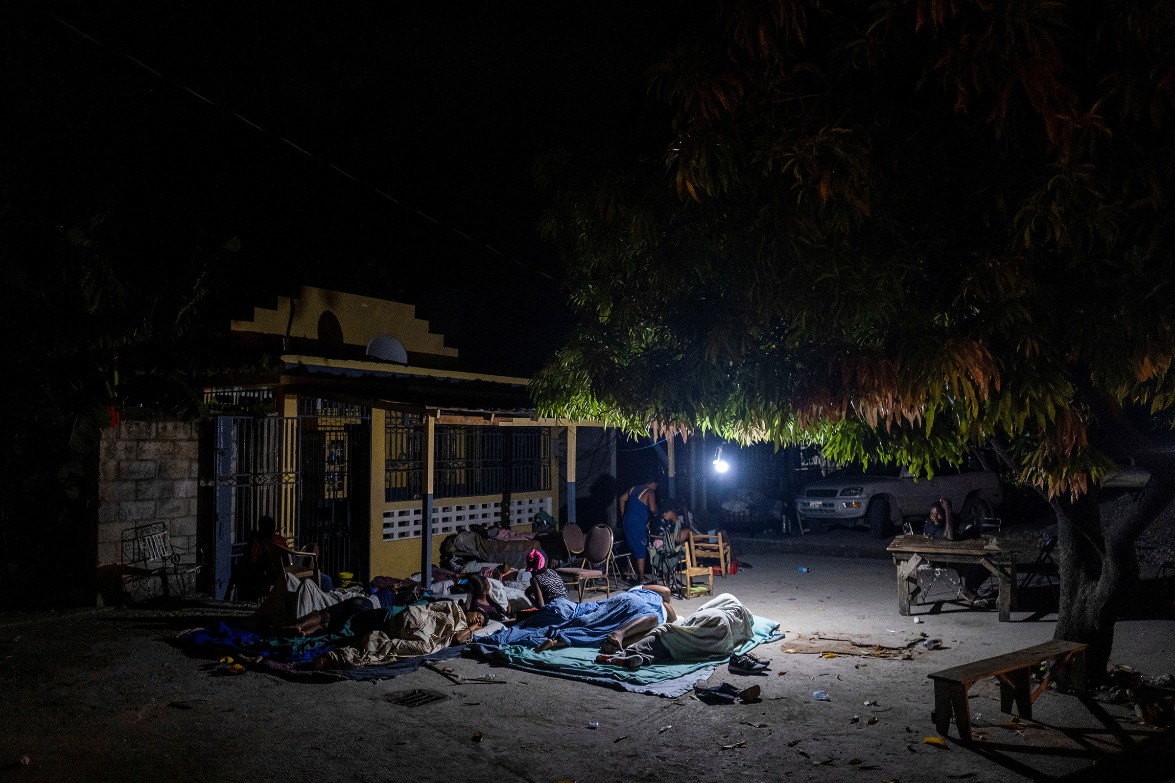 People rest outside their home after tremors shook buildings in Les Cayes on Aug. 19.