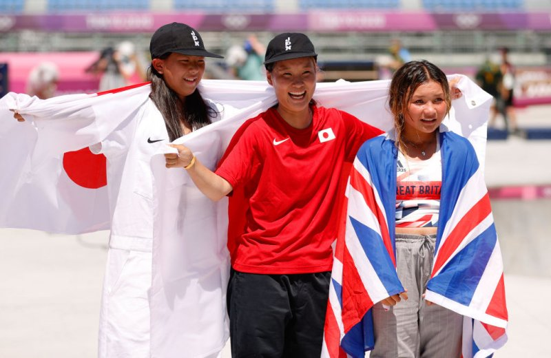 Japan's Sakura Yosozumi (center) and Kokona Hiraki (left) celebrate after winning gold and silver, respectively, in the Women's Skateboarding Park Finals at the Tokyo 2020 Olympic Games at Ariake Urban Sports Park on August 4, 2021. Sky Brown of Team Great Britain won bronze.