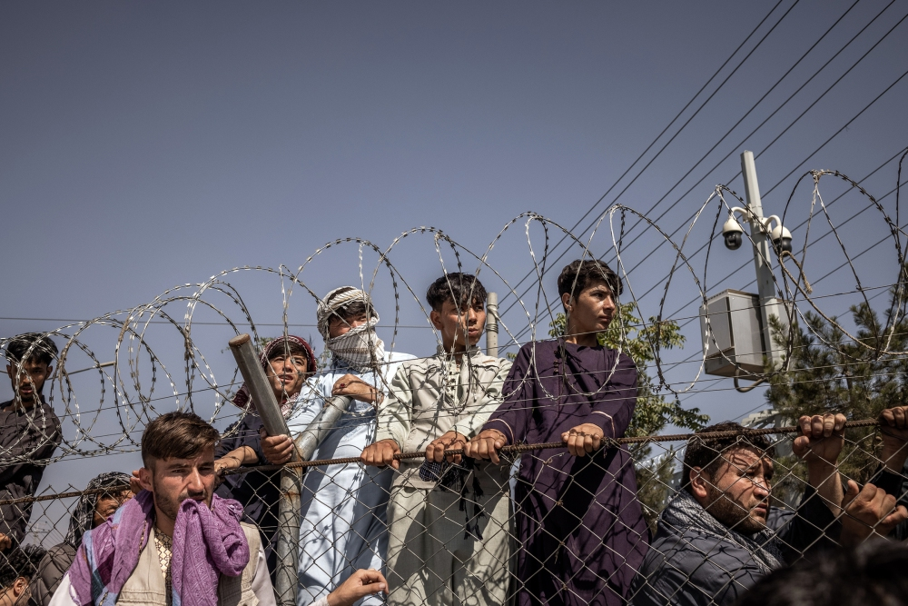 People seeking to leave Kabul gather at the international airport on Aug. 16, 2021.