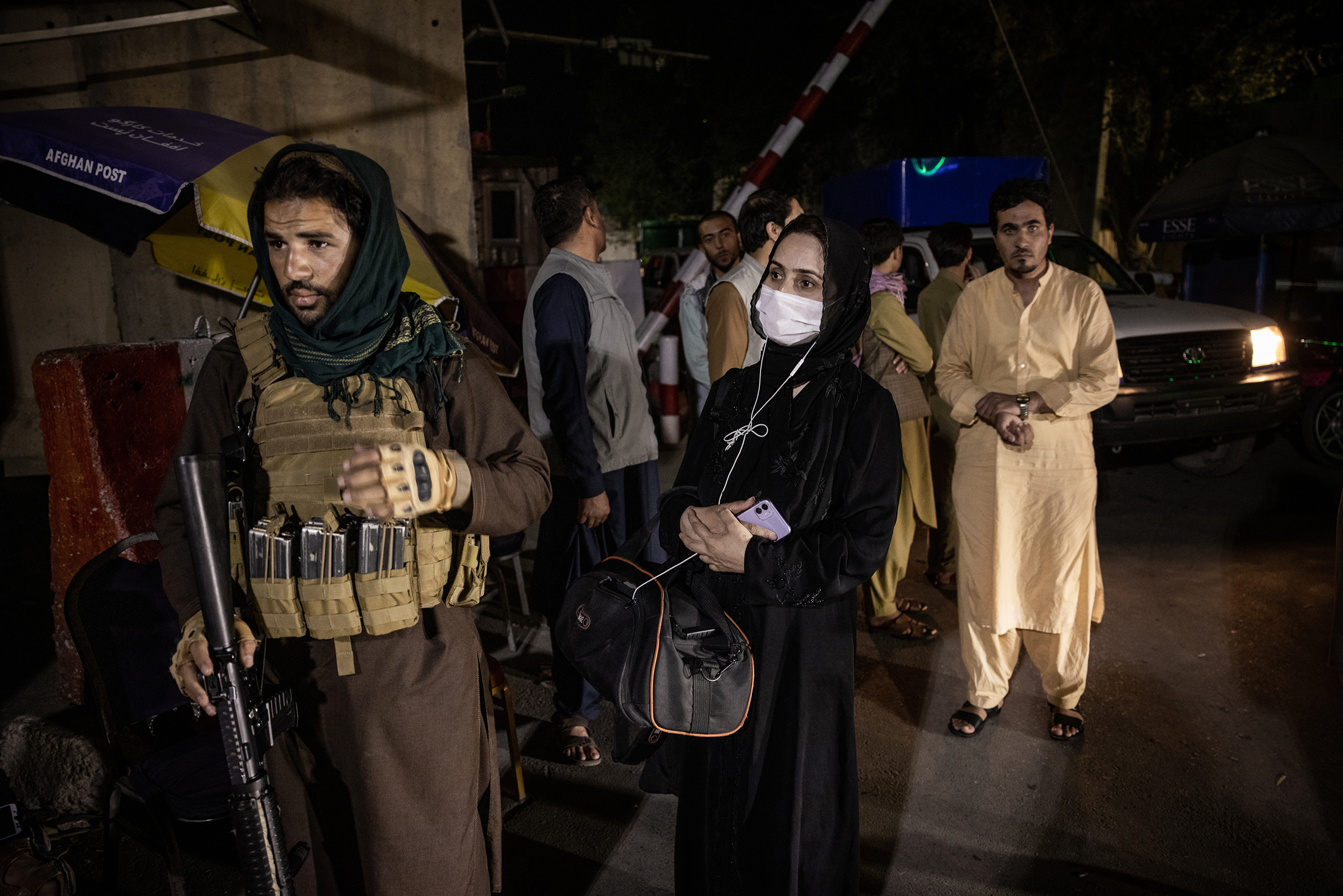 Zahra Nabi, a female journalist working for Bano TV, near Taliban fighters at a checkpoint after the first Taliban news conference in Kabul on Aug. 17, two days after their takeover.