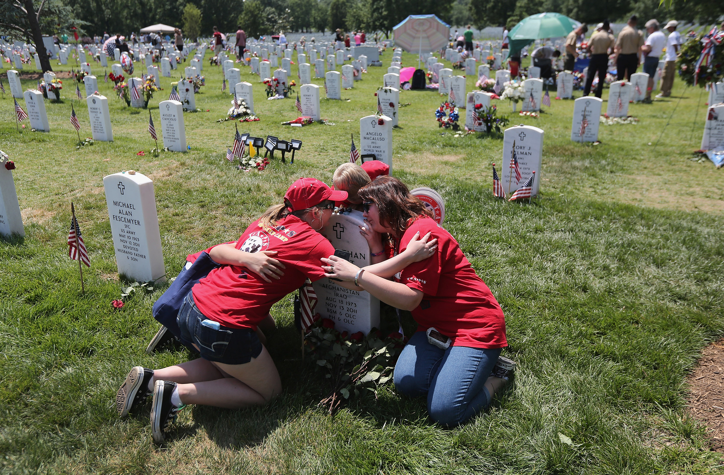 Leanne McCain, right, and her children embrace over her slain husband's grave at Arlington National Cemetery on May 28, 2012. Her husband, father-of-four Army SFC Johnathan McCain, was killed by a roadside bomb in Afghanistan in November 2011.