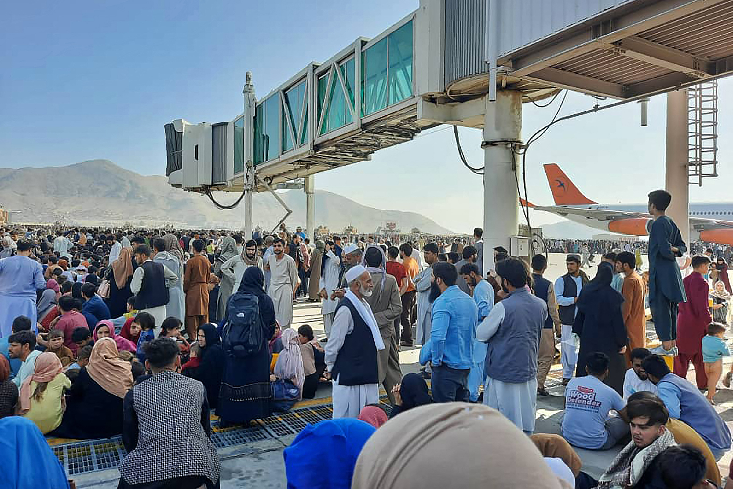 Afghans fleeing the Taliban's arrival in Kabul crowd the tarmac of the airport on Aug. 16, 2021.