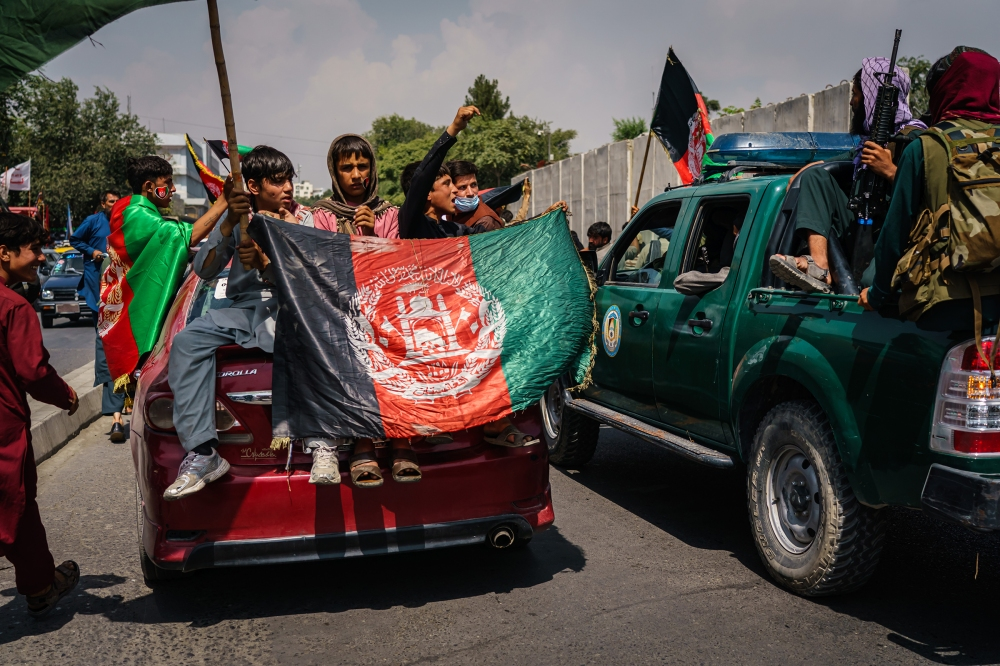 Afghans march while carrying banners and the flag of the Islamic Republic of Afghanistan, despite the presence of Taliban fighters, in Kabul on Aug. 19, 2021.