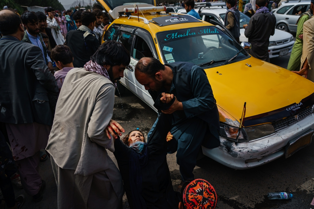 Men try to help a wounded woman and her child, who was also injured, after Taliban fighters use gunfire, whips, sticks and sharp objects to maintain control over a crowd of thousands waiting outside the airport in Kabul on Aug. 17, 2021.