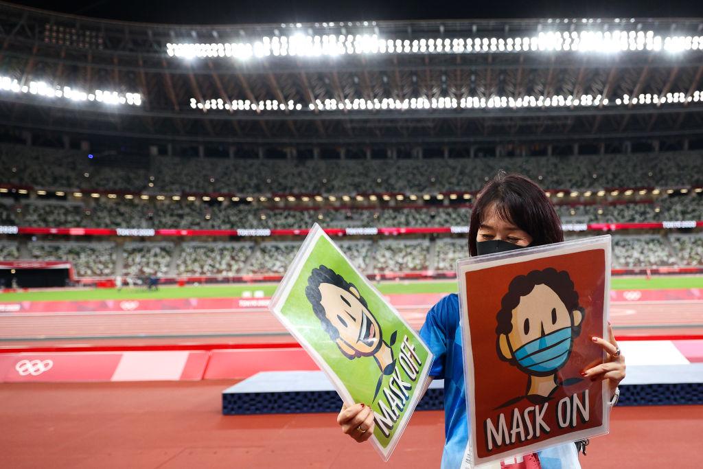 عضو فريق التصوير توموكو ميزوشيما يحمل لافتات القناع والقناع في اليوم الرابع عشر من دورة الألعاب الأولمبية في طوكيو 2020 في الاستاد الأولمبي في 6 أغسطس 2021 في طوكيو ، اليابان.