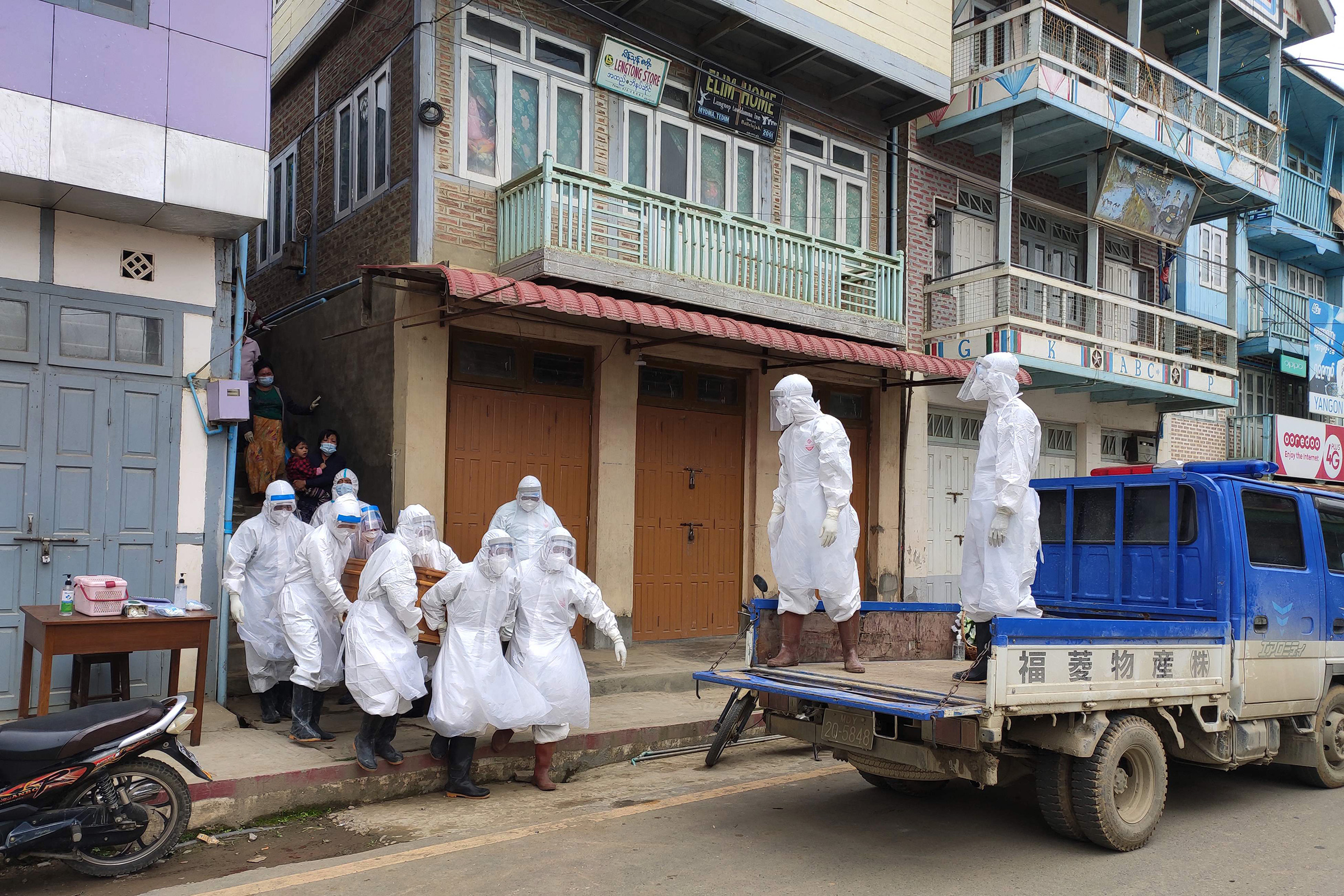 This handout photo from local media group Tedim Post taken and released on June 29 shows health workers carrying a coffin bearing the remains of a Covid-19 coronavirus victim who died at home in Tedim, western Chin state.