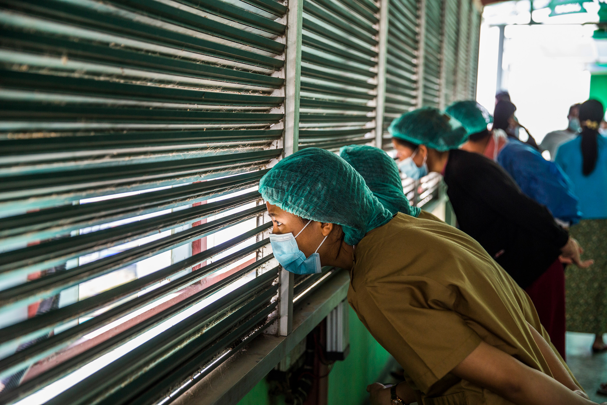 Health care workers watch protesters demonstrate against Myanmar's military coup in Myanmar's capital of Yangon, Feb. 28.