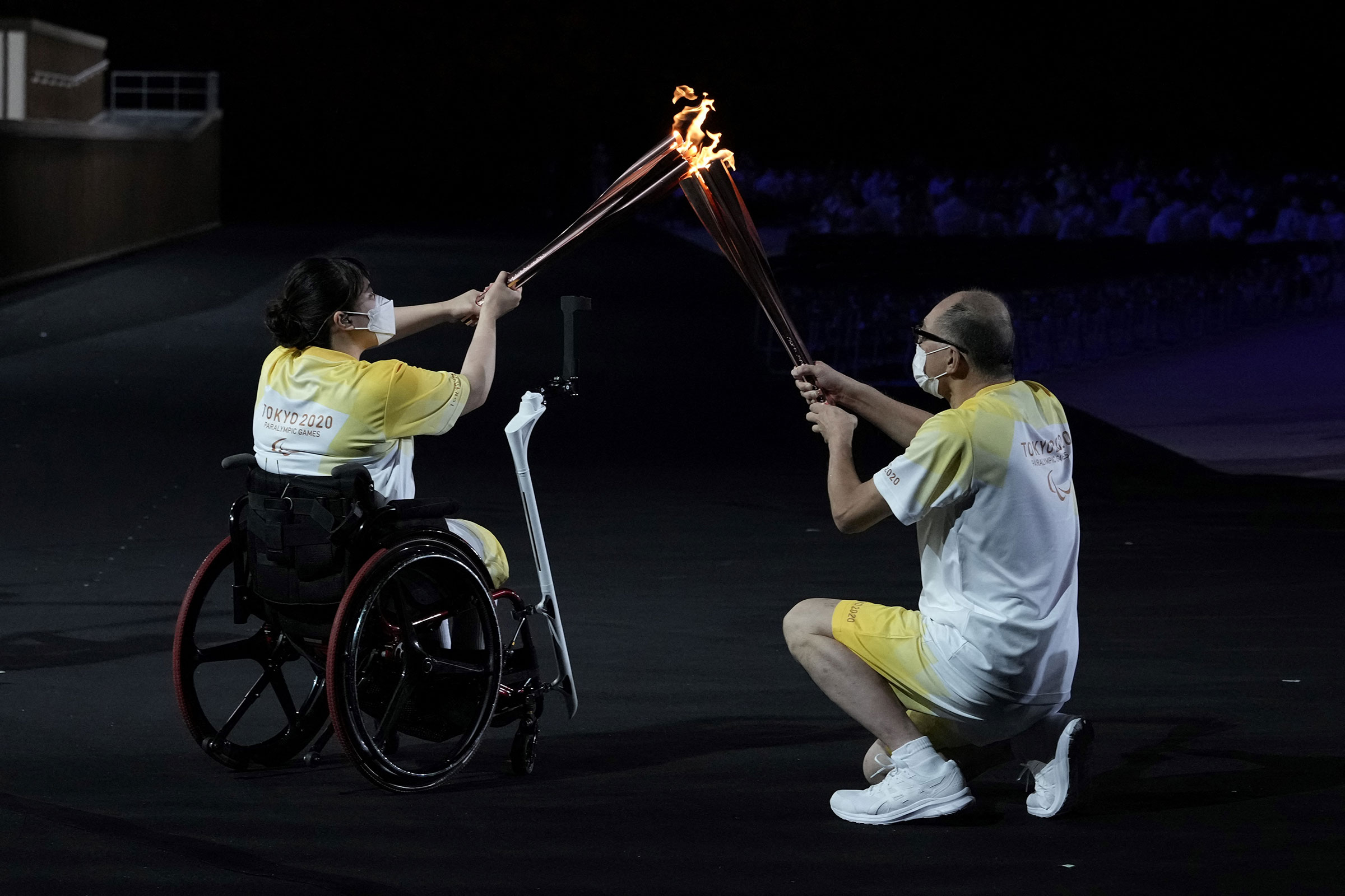 The Paralympic flame is passed between torchbearers during the opening ceremony for the Tokyo 2020 Paralympic Games at the Olympic Stadium in Tokyo on August 24, 2021.