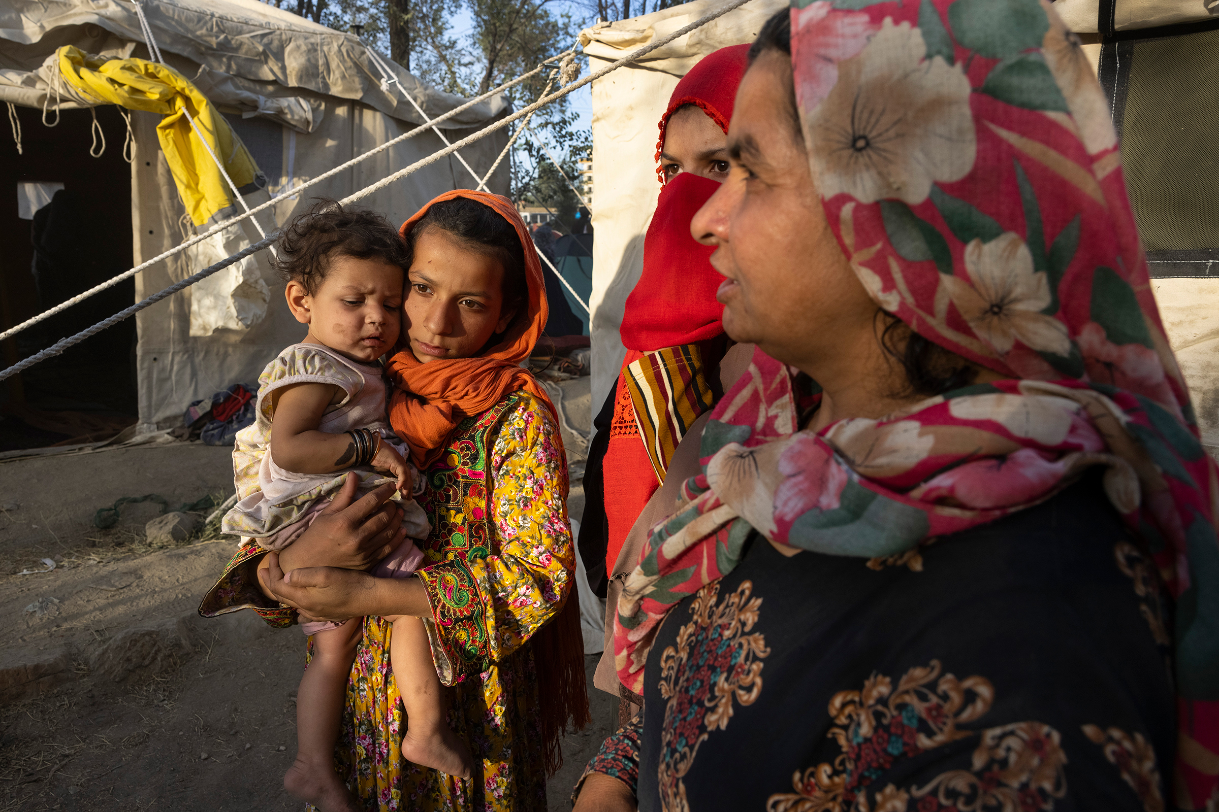 Halida, an 11-year-old whose father was killed by the Taliban, holds her eight-month-old cousin, Shafika, alongside family members as Afghans from the northern provinces arrive at a makeshift camp in Kabul on Aug. 10, 2021. Five days later, the Taliban took control of Kabul.