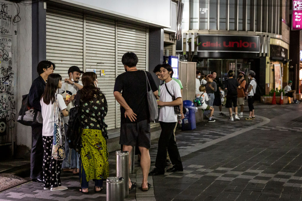 People stand in the street and drink on August 5, 2021 in Tokyo, Japan.